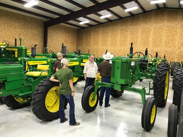 Hired Hand customers Teresa Sparger, Red McCombs Ranch and Kaitlyn Moss, Moss Longhorns admiring Lynn's John Deere tractor collection.